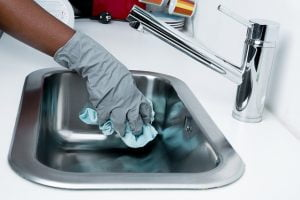 hand with glove cleaning stainless steel sink
