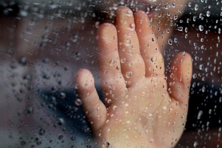 kid hand on window on rainy day